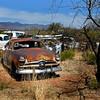 Old Ford sedan winking at the camera while rusting away in desert southwest junkyard.