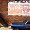 Old Cadillac next to a historic Colonial Bread Sign.